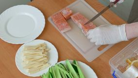 Chef cutting slices of salmon for sushi stock video