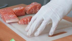 Chef cutting slices of salmon for sushi stock video footage