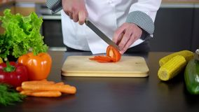 Chef cutting tomato on board in kitchen stock video