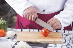 Chef cutting Tomato with knife befoer cooking Royalty Free Stock Photo