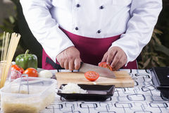 Chef cutting Tomato with knife befoer cooking Stock Photo