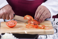 Chef cutting Tomato with knife before cooking Stock Photography