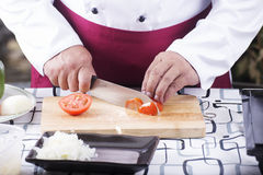 Chef cutting Tomato with knife before cooking Royalty Free Stock Image