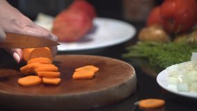 Chef cutting up an carrot with a knife stock video footage