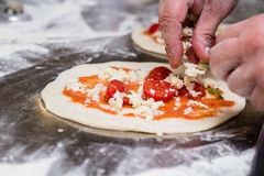 Chef cutting up mozzarella cheese on pizza dough Stock Photo