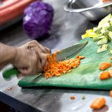 A chef cutting vegetables for food preparation stock images
