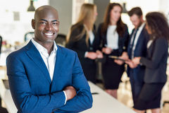 Chef d'homme d'affaires dans le bureau moderne avec travailler d'hommes d'affaires Image stock