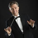Chef d'orchestre heureux Gesturing While Directing de musique avec son bâton photographie stock libre de droits