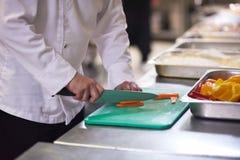 Chef dans des légumes de tranche de cuisine d'hôtel avec le couteau Photographie stock