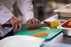 Chef dans des légumes de tranche de cuisine d'hôtel avec le couteau Photographie stock libre de droits