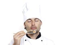 Chef dans le chapeau du chef avec des sushi Photos stock