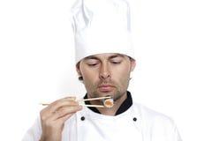 Chef dans le chapeau du chef avec des sushi Photographie stock