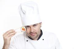 Chef dans le chapeau du chef avec des sushi Photographie stock libre de droits