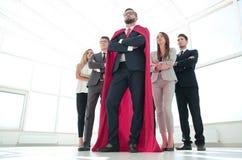 Chef dans le manteau rouge et l'équipe d'affaires se tenant ensemble images stock