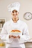 Chef dans les blancs retenant fièrement le bol de nourriture Photo stock