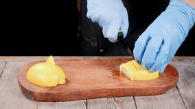 Chef dans les gants coupant en tranches le citron sur la planche à découper en bois Nourriture de restaurant roucoulant Mouvement banque de vidéos