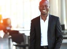 Chef de file des affaires afro-américain regardant l'appareil-photo dans l'environnement de travail photo stock