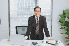Chef de file des affaires asiatique supérieur sûr se tenant dans le bureau Photos stock
