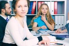 Chef de file des affaires féminin s'asseyant devant son équipe Concept sérieux d'affaires et d'association Image stock