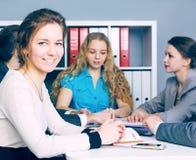 Chef de file des affaires féminin s'asseyant devant son équipe Concept sérieux d'affaires et d'association Photo stock