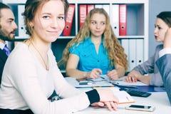 Chef de file des affaires féminin de sourire s'asseyant devant son équipe Concept sérieux d'affaires et d'association Images libres de droits