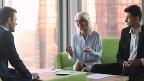 Chef de file des affaires mûr parlant aux associés divers lors de la réunion internationale banque de vidéos