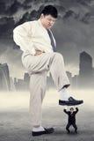Chef de file des affaires marchant le petit employé photo libre de droits