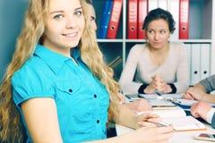 Chef de file des affaires de sourire féminin s'asseyant devant son équipe Concept sérieux d'affaires et d'association Photo stock
