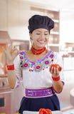 Chef de jeune femme utilisant le chemisier andin traditionnel, chapeau à cuire noir, supportant la tomate pour l'appareil-photo s photos stock