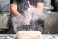 Chef de pâtisserie battant ses mains avec de la farine tout en faisant la pâte images stock