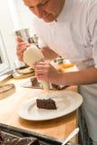 Chef de pâtisserie décorant le gâteau avec le givrage photo libre de droits