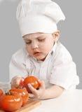 Chef de petit garçon faisant cuire des tomates Images libres de droits