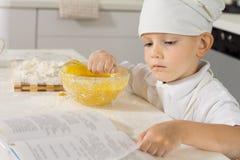 Chef de petit garçon vérifiant sa recette comme il fait cuire au four Image stock