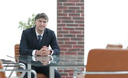 Chef de projet s'asseyant à une table dans une salle de conférence vide photo stock
