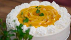 Chef de repostería adornado con la torta poner crema hecha en casa del melocotón de la menta con la menta metrajes