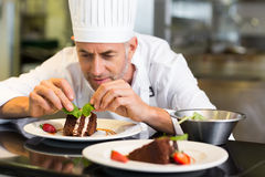 Chef de repostería de sexo masculino concentrado que adorna el postre en cocina Fotos de archivo libres de regalías