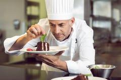 Chef de repostería de sexo masculino concentrado que adorna el postre en cocina Imagen de archivo