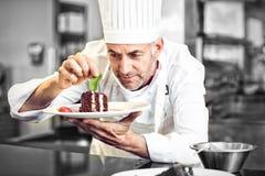 Chef de repostería de sexo masculino concentrado que adorna el postre en cocina Foto de archivo