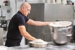 Chef de repostería profesional que bate la crema en cazuela grande en la cocina de la tienda de pasteles imagen de archivo libre de regalías