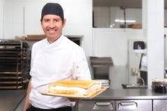 Chef de repostería que sonríe con una torta en sus manos en la tienda de pasteles foto de archivo