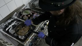 Chef de restaurant faisant cuire l'assaisonnement et grillant le mélange de la viande et des légumes exotiques dans la casserole banque de vidéos