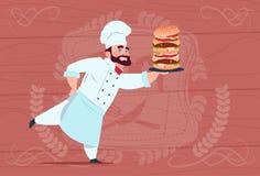 Chef de sourire de restaurant de bande dessinée de Hold Big Burger de cuisinier de chef dans l'uniforme blanc au-dessus du fond t Image libre de droits