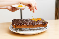 Chef decorate the cake with orange chips Stock Images