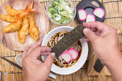 Chef decorated tempura udon wth dried seaweed. / Cooking Tempura Udon concept stock photography
