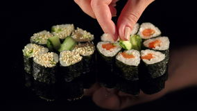 The chef decorates cucumber sushi before serving. stock video footage