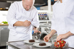 Chef decorates dessert cake with chocolate sauce in kitchen Stock Images