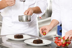 Chef decorates dessert cake with chocolate sauce in kitchen Royalty Free Stock Photo