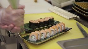The chef decorates ready sushi rolls with wasabi in the restaurant kitchen. stock footage