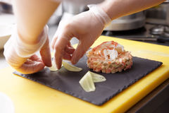Chef is decorating crab salad with cucumber slices Royalty Free Stock Photography