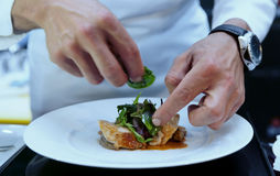 Chef is decorating delicious dish Royalty Free Stock Photos